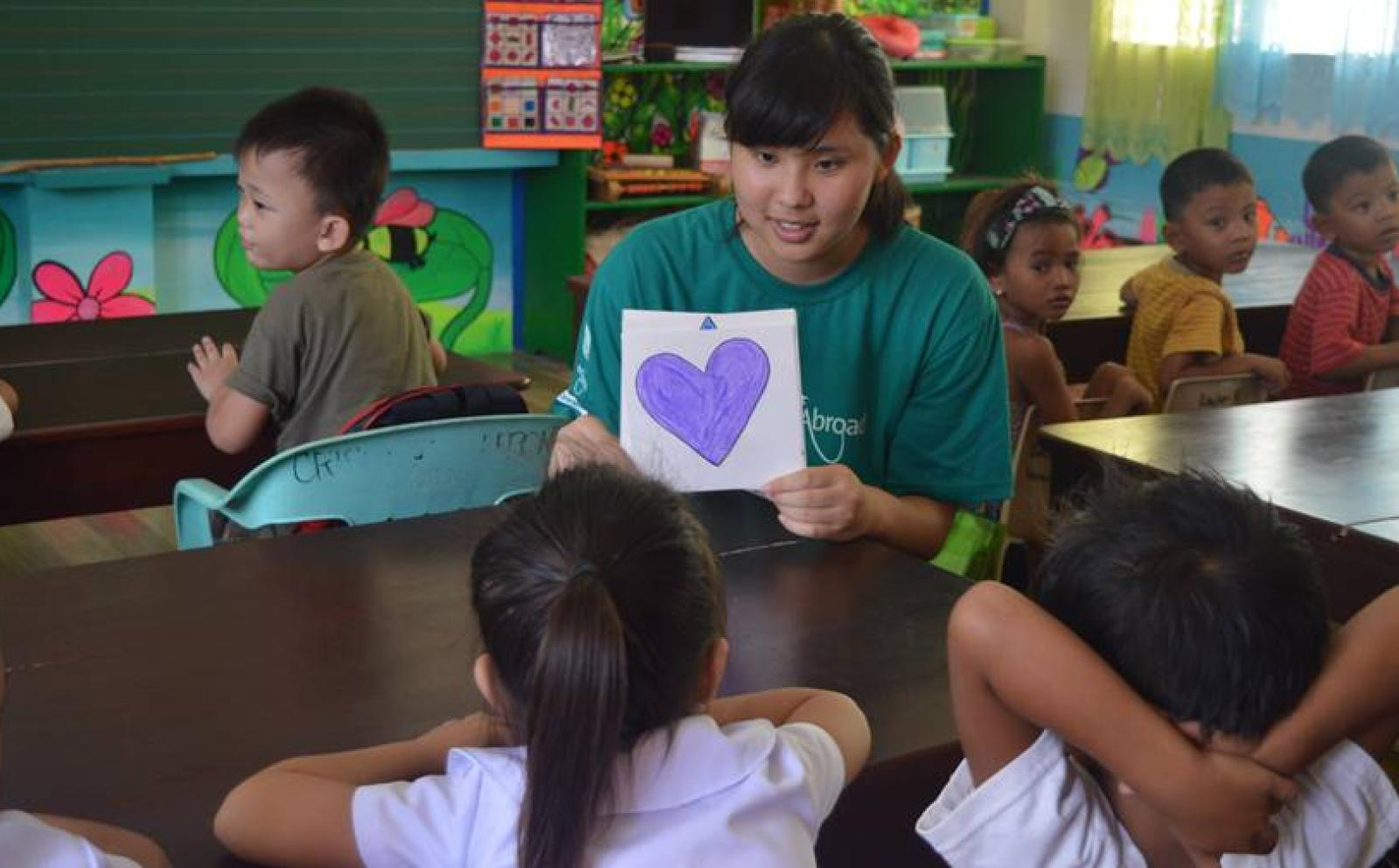 A Japanese Childcare volunteer teaches students about shapes on the Childcare project in the Philippines